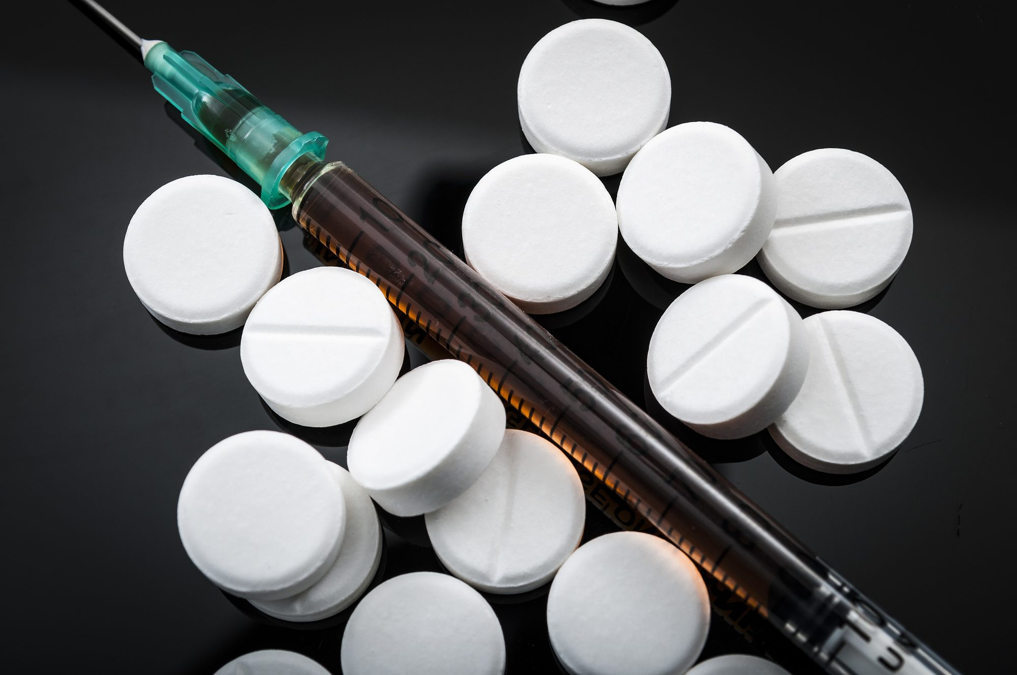 Opioid epidemic and drug abuse concept with closeup on a heroin syringe or other narcotics surrounded by scattered prescription opioids. Oxycodone is the generic name for a range of opioid painkillers